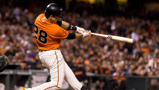 Giants catcher Buster Posey hits a two-run home run against the Cardinals.