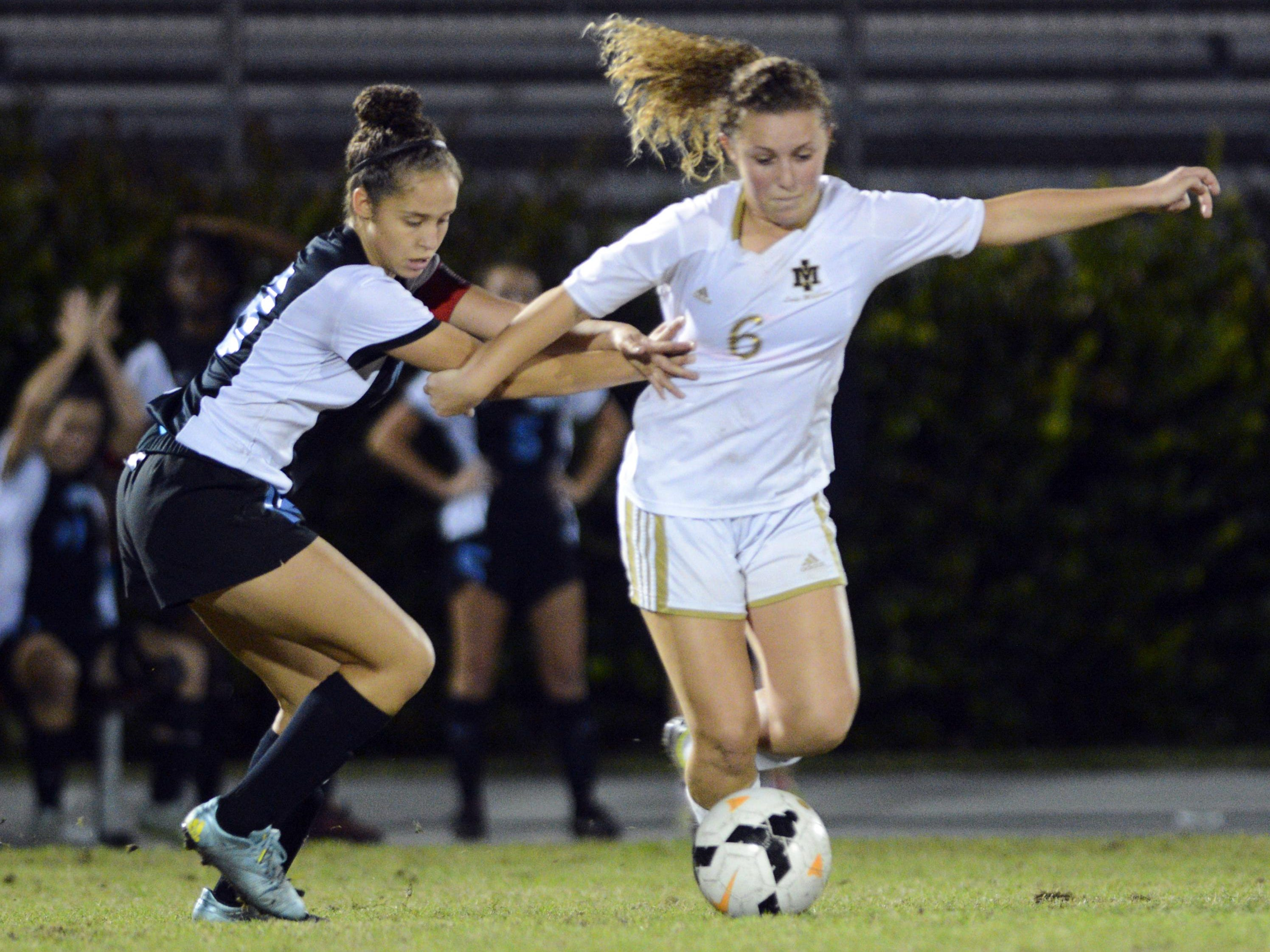 Rockledge's Savannah Henriquez (18) battles with Julia Martin (6) of Merritt Island during their district championship game Friday evening.