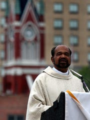 With the steeple of Saint Mathew Catholic Church in the background the Rev. Joseph Puthuppally leads Easter Sunday Mass at Anna Gray Noe Park in Monroe.