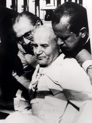 Pope John Paul II is assisted after he was shot and wounded by Mehmet Ali Agca in St. Peter's Square on May 13, 1981.