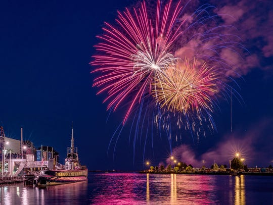 Fireworks explode over the Manitowoc River and the