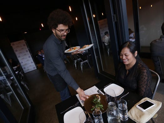 Selden Standard server Mikael Addae brings a dish to