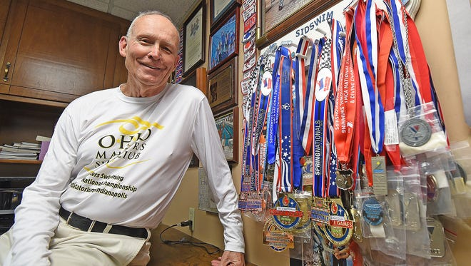 Sid Hall poses in his home office with the many swimming medals he has won.