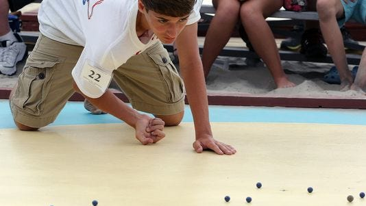 Dominic Rudakevych, 13, of Middletown, Md., shoots during the championship round of the 91st annual National Marbles Tournament at Ringer Stadium on the beach in Wildwood, N.J., Thursday, June 19, 2014. Rudakevych won the boys' title.
