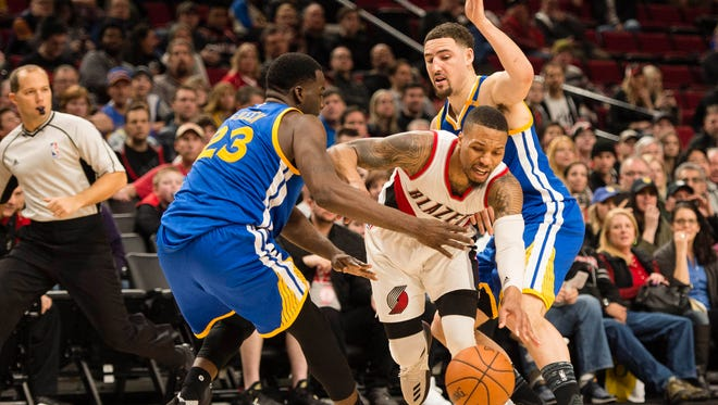 Portland Trail Blazers guard Damian Lillard breaks through a double team defense by Golden State Warriors forward Draymond Green and guard Klay Thompson.
