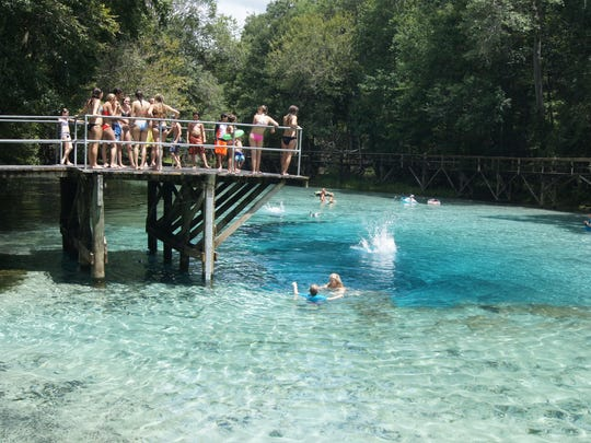 """Blue Springs in Gilchrist County is crystal blue """"Shangri-la"""" just west of High Springs and reminiscent of a """"Central Florida"""" summer camp, swimmers jump from a huge wooden diving platform into the crystal clear bubbly water."""