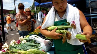 Va Vang with Vang Produce scoops up a handful of corn at the Collierville Farmers Market.