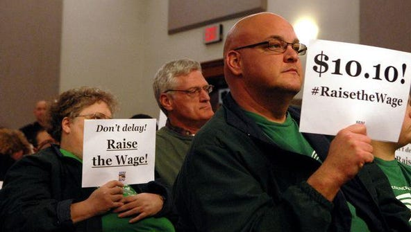 Bo Johnson holds a sign in support of a minimum wage