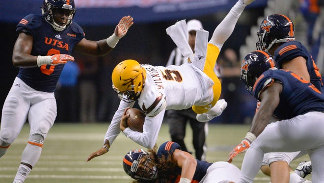 Arizona State quarterback Manny Wilkins (5) is taken down by UTSA defenders during the second half of an NCAA collegepfootball game, Friday, Sept. 16, 2016, in San Antonio. Arizona State won 32-28.