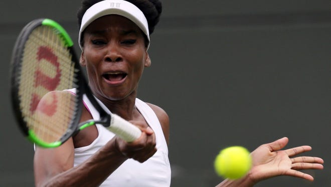 Venus Williams of the United States returns to Belgium's Elise Mertens during their Women's Singles Match on the opening day at the Wimbledon Tennis Championships in London Monday, July 3, 2017.