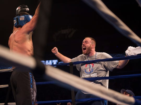 Guns' Tobin Riney celebrates with Guns coach AJ Naas after his fight during the Guns and Hoses fight night at the Ford Center on Saturday, April 7, 2018.