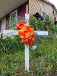 """A small wooden cross reading, """"In loving memory of"""