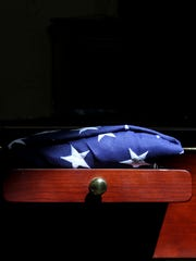 A flag sits next to the cremated remains of Master Sgt. David Montoya on Tuesday during a memorial service  at the New Mexico National Guard Armory in Farmington.