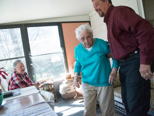 With Lynda Stamey looking on, Randy Martin helps Mozelle Smith up to getting lunch ready.