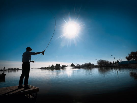 """MARK LAMBIEÑEL PASO TIMES  Fishermen try their luck at Ascarate Lake on a warm Thursday afternoon. The lake was stocked with 2000 pounds of trout on Wednesday. """