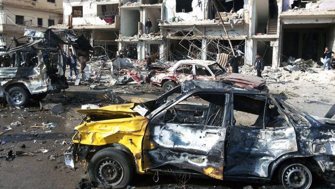 Syrian citizens gather at the scene where two blasts exploded in the pro-government neighborhood of Zahraa, in Homs province on Sunday.