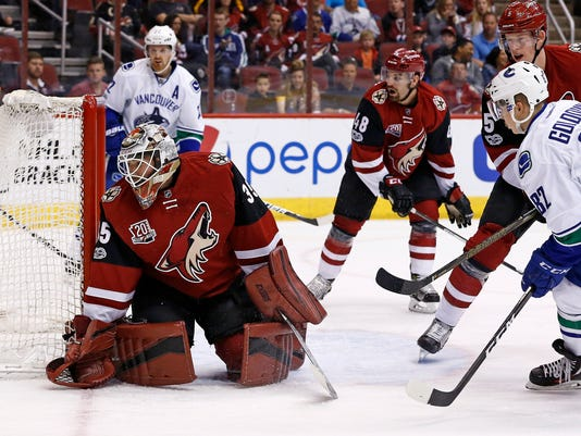 Vancouver Canucks' Nikolay Goldobin (82) scores a goal against Arizona Coyotes' Louis Domingue (35) as Coyotes' Connor Murphy (5), Jordan Martinook (48) and Canucks' Daniel Sedin (22) look on during the first period of an NHL hockey game Thursday, April 6, 2017, in Glendale, Ariz. (AP Photo/Ross D. Franklin)