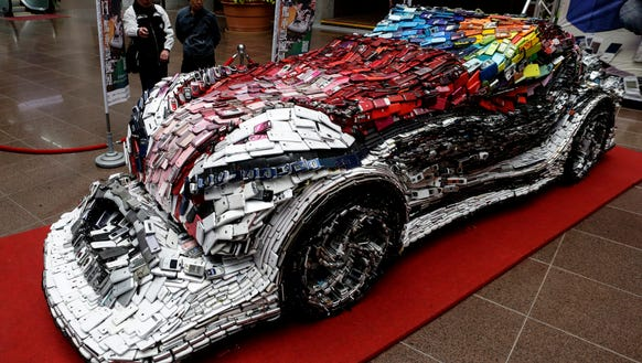 Visitors view an art installation car made from mobile