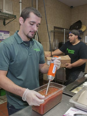 Employees Brett Emde (left) Brick and Joeel Moran, Brick, prepare food at Bubbakoo's Burritos in Jackson.