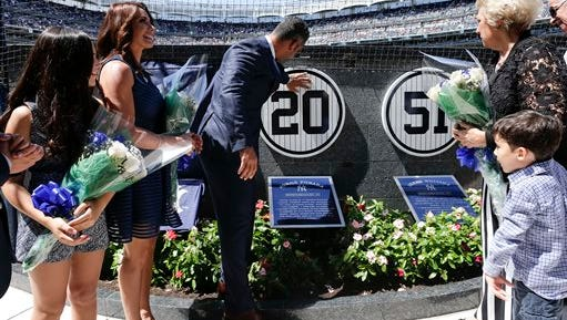 Accompanied by family members, former Yankees catcher Jorge Posada touches a plague with his jersey number on a wall in Monument Park during a ceremony retiring his number before a baseball game against the Cleveland Indians, Saturday, Aug. 22, 2015, in New York.