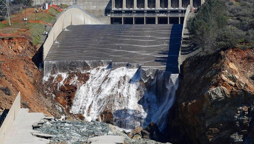 FILE - In this Feb. 28, 2017 file photo, water goes down Oroville Dam's crippled spillway in Oroville, Calif. Over six days, operators of the tallest dam in the United States, struggled to figure out their next move after raging floodwaters from California's wettest winter in decades gouged a hole the size of a football field in the dam's main water-release spillway.