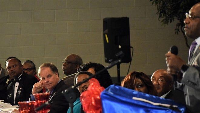 Democratic Senate nominee Doug Jones listens to a speech from Sen. Bobby Singleton, D-Greensboro, at a dinner in Greensboro on Nov. 26, 2017.