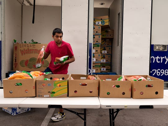 Noah Stubblefield, 16, distributes fresh produce while volunteering at the Meals of Hope Mobile Food Pantry in the parking lot of the Greater Naples YMCA on Tuesday, Nov. 15, 2016, in North Naples. Stubblefield has volunteered at the food pantry since the beginning of summer.