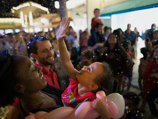 Four-year-old Jade Whitaker of Naples rejoices in a snow display with her mother, Jenny Theodore, left, and friend Ivan Torres, on Nov. 25, 2016 at the Village Shops on Venetian Bay.