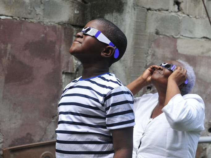 People look at a rare solar eclipse wearing glasses offered by Gabonese Red Cross on Nov. 3 in Libreville. The west African nation of Gabon get peak viewing of the total eclipse as it swept over a path nearly 37 miles wide.