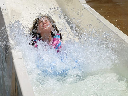 Kamryn Wood, 6, splashes to a stop after riding the