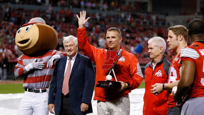 """Ohio State football coach Urban Meyer waves to fans as he accepts the first """"Reds Country Athletic Achievement Award"""" for the team's NCAA championship, from Cincinnati Reds President and CEO Bob Castellini, second from left, before the Reds' baseball game against the Pittsburgh Pirates on Wednesday, April 8, 2015, in Cincinnati. With them is Brutus Buckeye."""