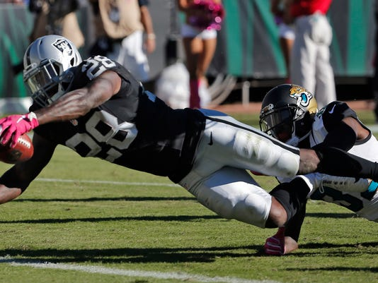 Oakland Raiders running back Latavius Murray (28) is tripped up by Jacksonville Jaguars free safety Tashaun Gipson (39) as he dives over the line for a score during the fourth quarter of an NFL football game Sunday, Oct. 23, 2016, in Jacksonville, Fla. (AP Photo/Stephen B. Morton)