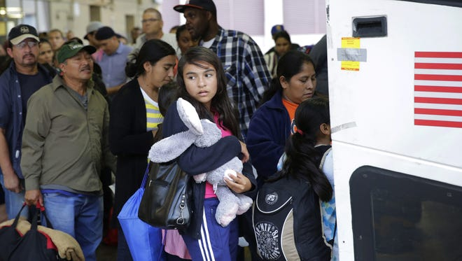 FILE - In this Tuesday, July 7, 2015, file photo, immigrants from El Salvador and Guatemala who entered the country illegally board a bus after they were released from a family detention center in San Antonio. With tens of thousands of Central American families arriving on the U.S.-Mexico border in the last two years, federal authorities have crafted a new plan to try to encourage more of them to show up for immigration court.