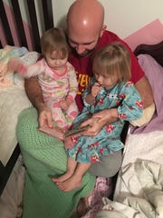 Casey reads to his daughters.