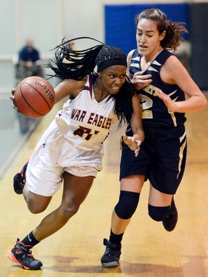 Holy Trinity's Paris Vergara closely guards Kiara Cadore of Astronaut during Thursday's district semifinal in the Holy Trinity gym.