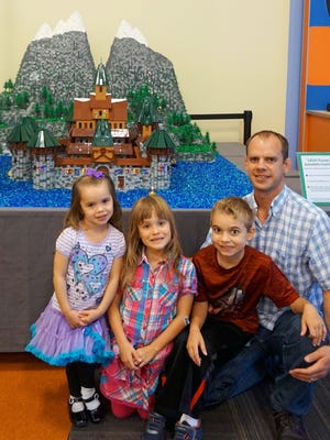 """Ben Pitchford, master Lego Builder, along with his children, starting left: Emmelyn, Amelia and Maxwell, in front of """"LEGO Arendelle Castle."""""""