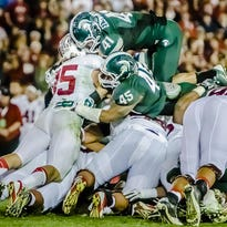 MSU's Darien Harris (45) and Kyler Elsworth (41) stop Stanford's Ryan Hewitt on a fourth-and-1 with 1:45 remaining in the Rose Bowl on Jan. 1, 2014 in Pasadena, California. It is one of the iconic plays in MSU football history.