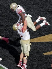 Florida State junior tailback Jacques Patrick (9) is lifted by offensive tackle Landon Dickerson (69) after his first half touchdown run against Wake Forest.