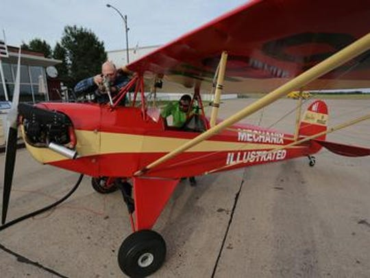 Kurt Mehre of Schofield refuels the Baby Ace at the Wausau Downtown Airport on July 24, 2014 as a group of Wausau-area aviators flew the plane to get enough hours on it to be able to fly it to EAA AirVenture in Oshkosh. Peeking inside the plane is flight instructor Steve Montgomery.