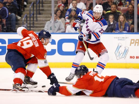 New York Rangers center Ryan Spooner (23) passes the puck past Florida Panthers defensemen Mike Matheson (19) and Mark Pysyk (13) during the first period of an NHL hockey game Saturday, March 10, 2018, in Sunrise, Fla. (AP Photo/Wilfredo Lee)