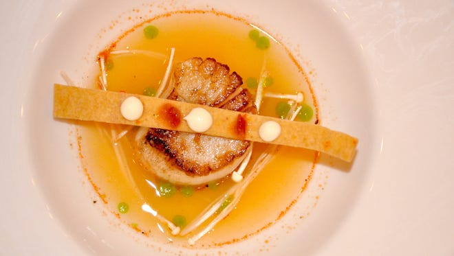Pan-seared dayboat scallop from the Jersey Shore, in a shrimp and kaffir lime consommé, with straw mushrooms, housemade Thai chili tuille (the cracker), chili paste, galangal aioli and dashi oil.