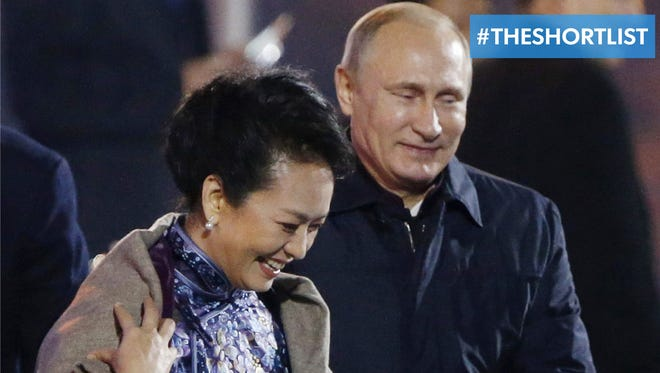 Russia's President Vladimir Putin puts a shawl on Peng Liyuan, wife of Chinese President Xi Jinping, at the Asia Pacific Economic Cooperation (APEC) summit in Beijing on Nov. 10.