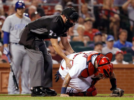 Home plate umpire Jim Reynolds checks on St. Louis Cardinals catcher Yadier Molina after Molina was hit on the mask by consecutive foul balls by Chicago Cubs' Kris Bryant during the seventh inning of a baseball game Monday, Sept. 25, 2017, in St. Louis. Molina left the game. (AP Photo/Jeff Roberson)