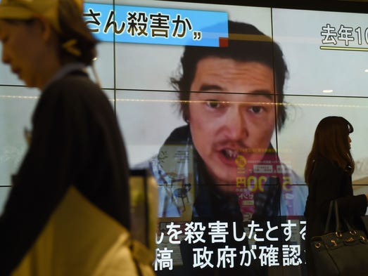 People in Tokyo walk past a big screen reporting that
