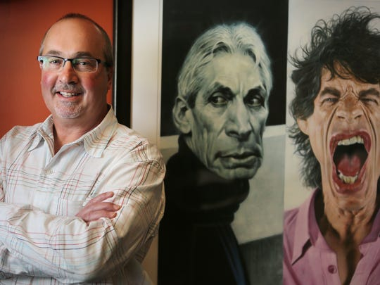 Scott Stienecker, president and CEO of independent concert promoter PromoWest Productions, is photographed in his Columbus office alongside images of The Rolling Stones' drummer Charlie Watts, center, and lead singer Mick Jagger.