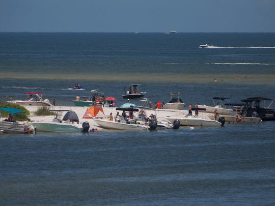Boaters line up on the beach at New Pass near Lover's