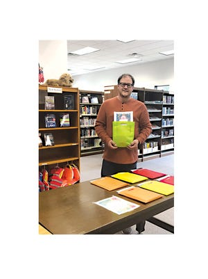 Andy Kelton, Library Director, is holding one of the weekly take home kits for the Summer Reading program.
