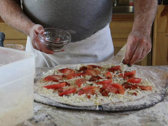 Bob Pfaff, founder of Left Coast, adds housemade tomato sauce to a pizza. The pizzas at the winery and vineyard are made in a wood-burning oven fueled by estate-grown oak.