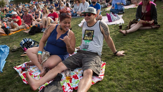 Angie Armstrong and Nate Moberg lay in the grass in front of the main stage at McDowell Mountain Music Festival on Sunday, Mar. 13, 2016 in Phoenix, Ariz.