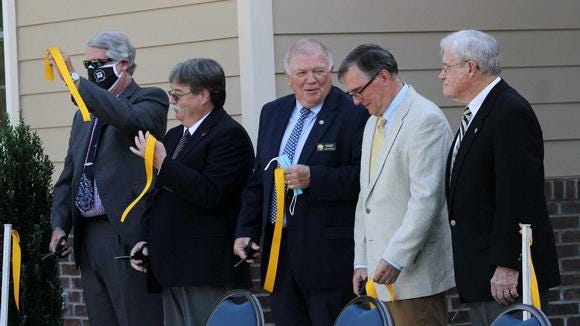 River Bend Town Council members Brian Leonard, Don Fogle, Harry 'Bud' McClard, Buddy Sheffield and Bud Van Slyke dedicate the new River Bend Municipal Building at a ribbon cutting ceremony held in River Bend, NC, July 16, 2020. The ceremony officially opens the building for municipal meeting rooms and town offices that include the River Bend Police Department. The new building was designed by The Walker Group of New Bern.